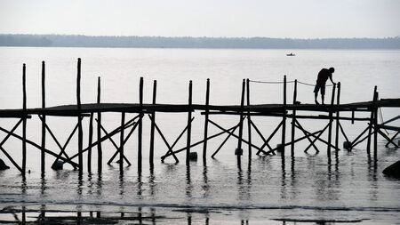 Silhouette of a wooden platform and a man standing early in the morning at a fishing village.