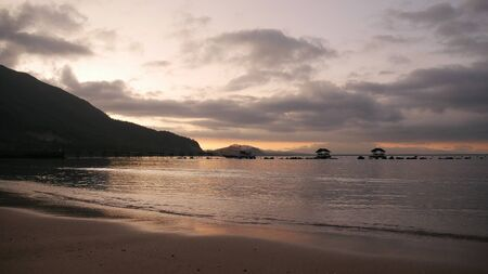 Medium wide shot of a golden sunrise breaking over the beach at Bonhomie Resort in Davao Oriental, Southern Philippines.