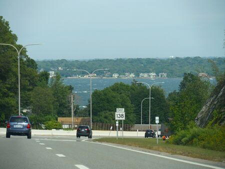 Jamestown, Rhode Island-September 2017: Wide shot of the bay with a roadside sign approaching the Jamestown Verrazzano Bridge.