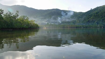 Early morning panoramic view of the mountains reflected in the lagoon of a fishing village in Banay Banay, Davao Oriental.