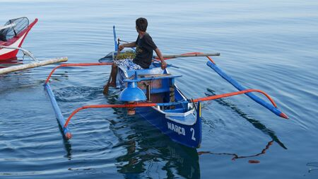 Banay Banay, Davao Oriental, Philippines - March 2016: A fisherman heads out in a blue outrigger boat at Punta Linao fishing village in the southern Philippines.