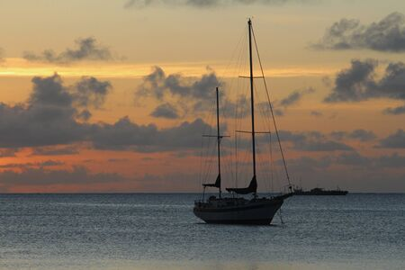 Silhouette of a sailboat seen after the sun has set and disappeared in the horizon