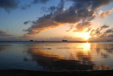 Stunning sunset and gorgeous clouds reflected in the lagoon of Saipan, Northern Mariana Islands.