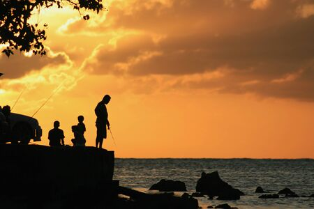 Silhouette of fishermen with fishing poles in the water at sunset