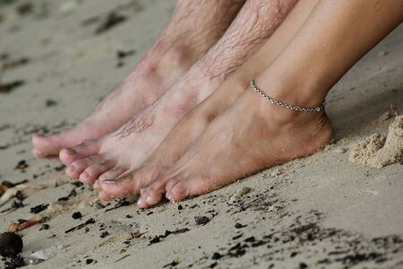 Wet feet of a man and a woman in the sand Stock Photo