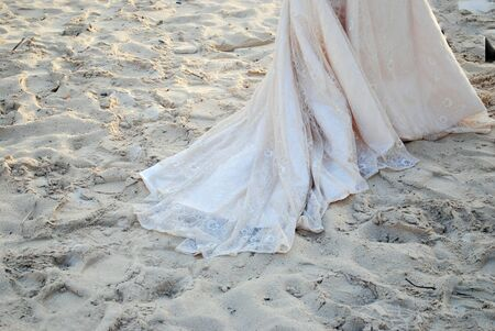 Hem of a white lace wedding gown trailing in the white sand at a tropical wedding Reklamní fotografie