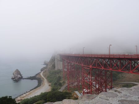 San Francisco, California-July 2018: Wide shot of the end part of the Golden Gate Bridge made invisible by a thick fog.