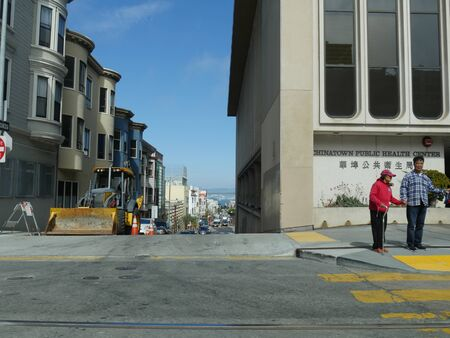 San Francisco, California-July 2018: Two people wait on the curb to cross the street infront of the Chinatown Public Health Center in San Francisco. Standard-Bild