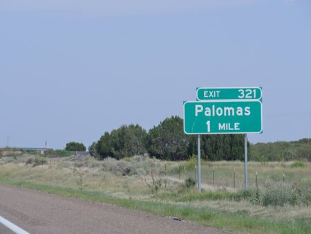 Directional sign on the highway with directions to Palomas, New Mexico.