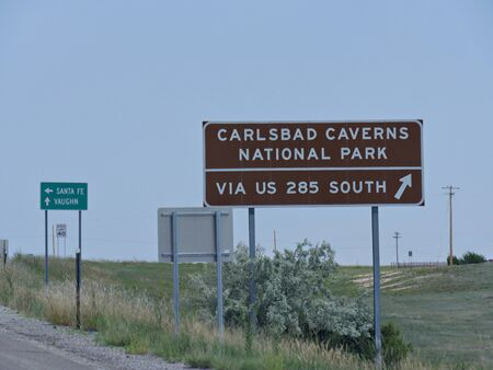 Medium close up shot of directional signs on the highway with directions to Carlsbad Caverns National Park in New Mexico.