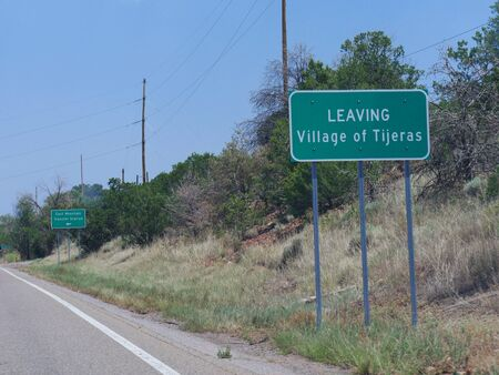 Directional signs on the road leaving the Village of Tijeras, New Mexico. Imagens