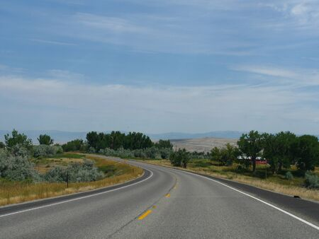 Winding road with scenic nature views in Wyoming, wide shot.