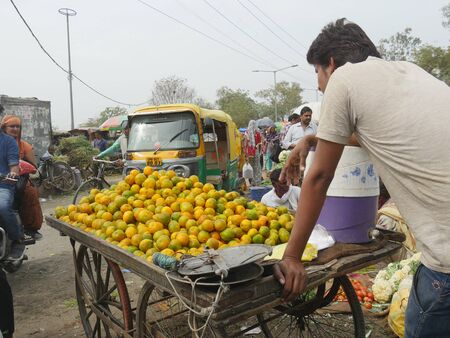 Agra, Uttar Pradesh, India- March 2018: A man pushes an improvised cart filled with citrus fruits at a street market in Agra. Stock Photo