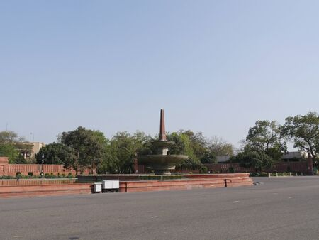 New Delhi, India- March 2018: Wide shot of a water fountain and park across from the Parliament building in New Delhi.