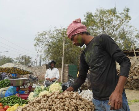 Agra, Uttar Pradesh, India- March 2018: A vendor arranges his display of ginger and other vegetables at a street market in Agra.