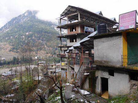 Manali, Himachal Pradesh, India- March 2018: Multi-storey residential building with snow-capped mountains in the background in Manali.