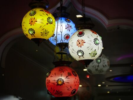 Agra, Uttar Pradesh, India- March 2018: Colorful lantern lights hang from the ceiilng of a restaurant in Agra.