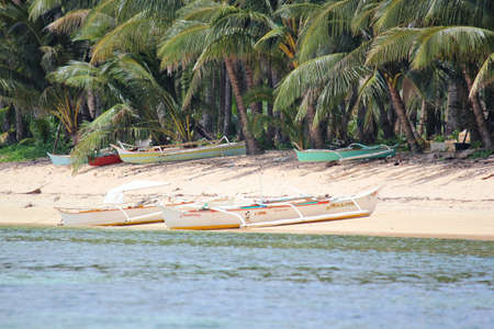 Surigao del Sur, Philippines- August 2014: Outrigger boats docked on the white sandy shore of a fishing village in one of the islands in Cantilan, Surigao del Sur.
