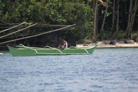 Surigao del Sur, Philippines- August 2014: A fisherman sets out in a green outrigger boat in Libtong Cove, Cantilan.
