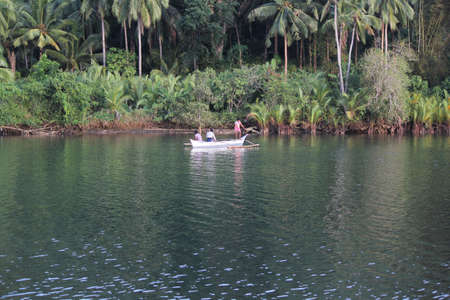 Surigao del Sur, Philippines- August 2014: Wide shot of the river with three people on a boat in Carrascal, Surigao del Sur. 新闻类图片