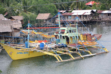Surigao del Sur, Philippines- August 2014: Colorful boats docked in the water with houses on stilts in a fishing village in Tandag City, Surigao del Sur.