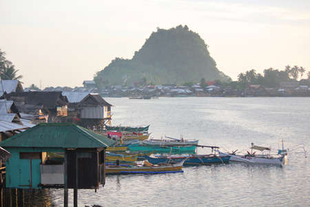 Surigao del Sur, Philippines- August 2014: Early morning scene in a fishing village with colorful boats and houses on stilts in Tandag City, Surigao del Sur.