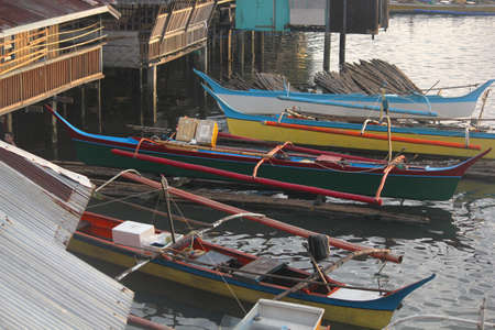 Surigao del Sur, Philippines- August 2014: Colorful boats tied to houses on stilts at a fishing village in Tandag City, Surigao del Sur.