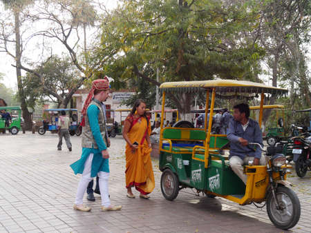 Agra, Uttar Pradesh, India- March 2018: A couple in colorful traditional Indian clothing gets ready to ride a rickshaw in Agra.
