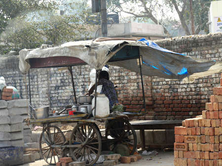 Mathura, Uttar Pradesh, India- March 2018: A man cooks food from a makeshift cart on the side of a street in Mathura.
