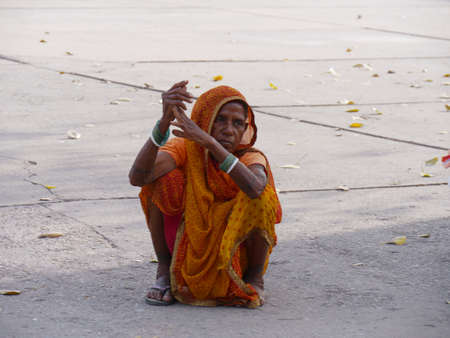 Agra, Uttar Pradesh, India- March 2018: A woman wearing traditional Indian clothing sits on the concrete at the grounds of Taj Mahal.