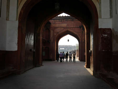 Agra, Uttar Pradesh, India- March 2018: Massive arches with people walking inside Agra Fort.