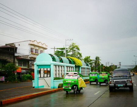 Tagum City, Philippines- March 2016: Rainy afternoon with tricycles, or improvised motorcycle with sidecars on the road in Tagum City.