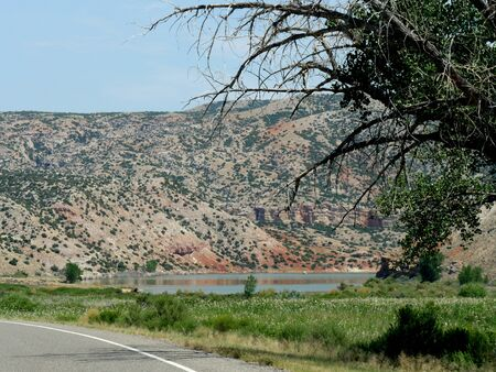 Landscape view by the highway in Wyoming, with a pond at the foot of a hill. Stockfoto
