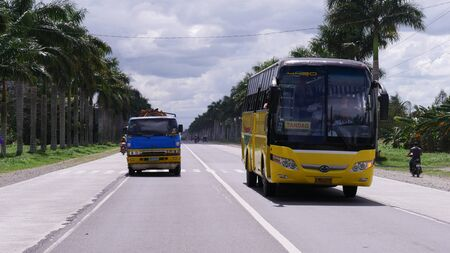 Tagum City, Philippines- March 2016: A truck and a bus for public transportation travels on the road in Tagum City.