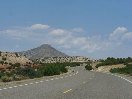 Wyoming-Montana stateline winding road with motorcyclists in the distance. Stockfoto