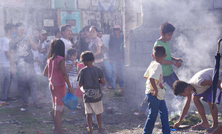 Tagum City, Philippines- March 2016: Following tradition, people walk over a small bonfire after burying a dead relative. Redactioneel
