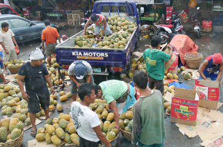 Tagum City, Philippines- March 2016: Buyers pick out pineapple fruits outside the public market in Tagum City. Redactioneel