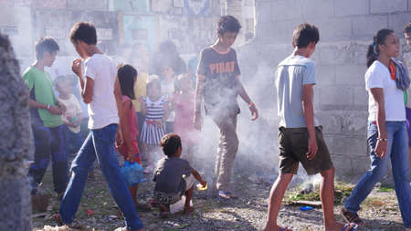 Tagum City, Philippines- March 2016: People walk over a small bonfire after burying a dead relative in the cemetery. It is one of the supersititions beliefs to ward off the evil spirits away. Redactioneel