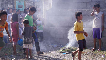 Tagum City, Philippines- March 2016: Following a superstitious belief, children walk over a small bonfire after burying a dead relative. Redactioneel