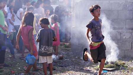 Tagum City, Philippines- March 2016: Following one of the many superstitious beliefs in the Philippines, children walk over a small bonfire after burying a dead relative.