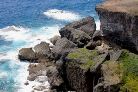 Deep cliffs and huge slabs of stones bordering a beautiful coastal in a tropical island