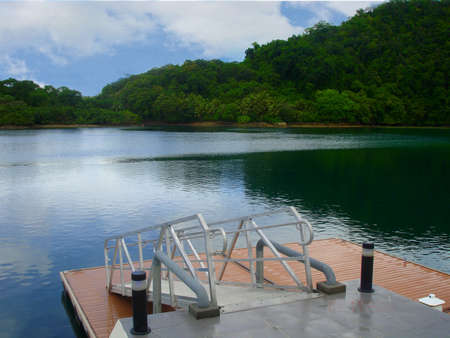 Floating dockWooden floating dock facing blue green waters of a lake, with lush jungles and blue clouds