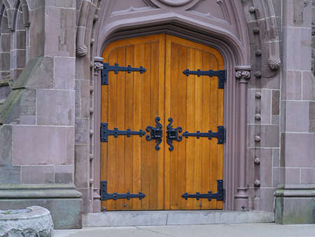 Old wooden heavy doors with antique knockers and door handles of an old church