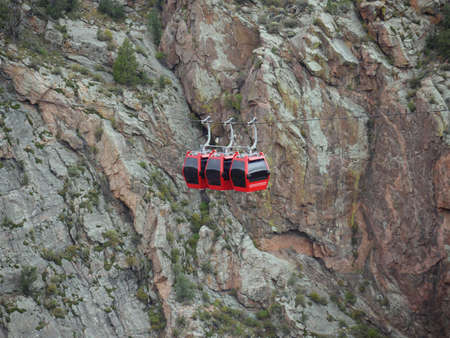 Red gondolas suspended over the Arkansas River at the Royal Gorge Bridge & Park in Fremont County, Colorado.
