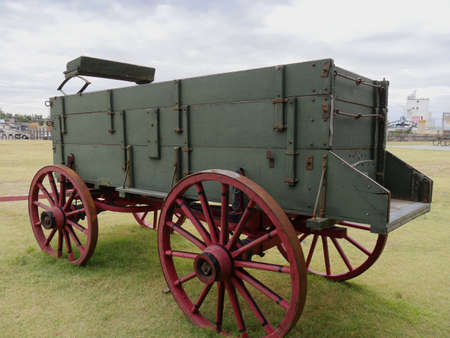 Vintage wagon with wheels painted in red and displayed outdoors in a park