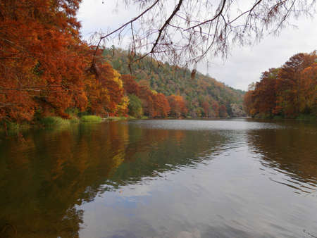 Wide shot of the Mountain Forks River at the Beavers Bend State Parks in Broken Bow, Oklahoma with colorful foliage in autumn Stock Photo