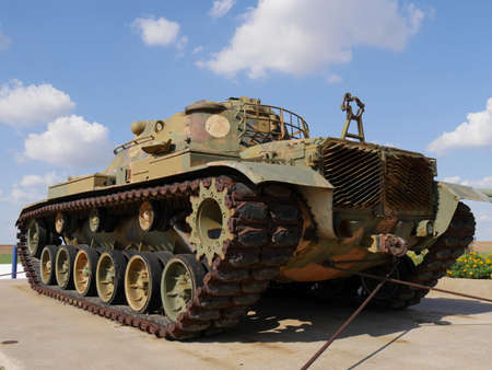 Military tank by the roadside with blue and white skies in the background with rusty parts