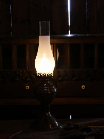 Lighted antique oil lamp in a dark room with wooden walls