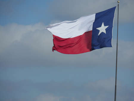 Texas state flag flying in the skies from a pole