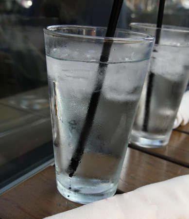 Tall glasses of ice-cold water with black straw Imagens